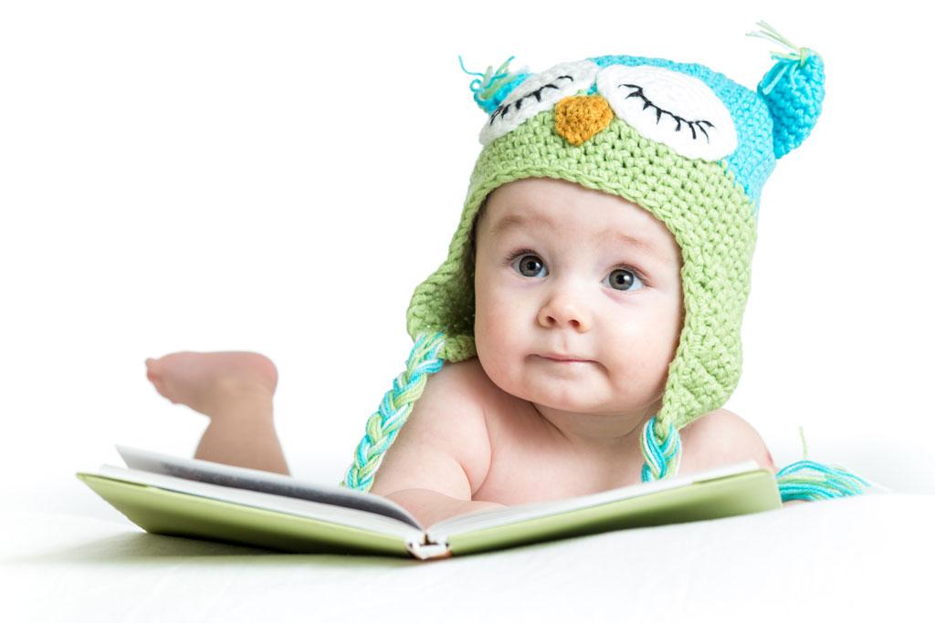 Bebê com touca de croche e livro