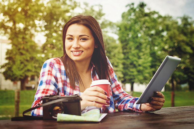 Estudante bonita com traços asiáticos sentada ao ar livre segurando um copo e um tablet com uma câmera na mesa