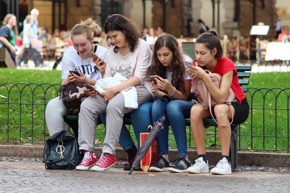 Meninas sentadas em uma praça mexendo no celular; usando o smartphone para navegar na internet ou falar no whatsapp