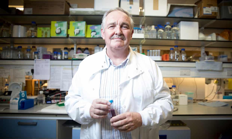 Cientista britânico David Nutt em seu laboratório segurando um frasco co m um líquido vermelho