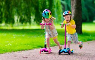Crianças brincando de patinete em parque