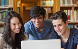 3 amigos estudando na frente de um notebook