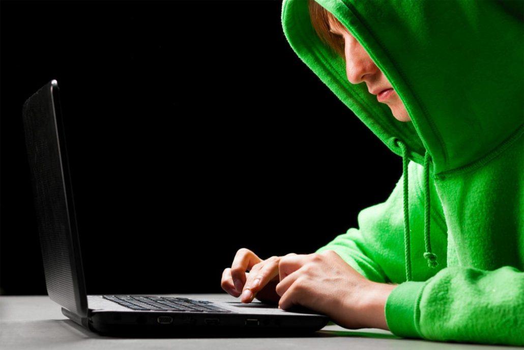 Adolescente com moletom e capuz verde digitando em notebook como um hacker
