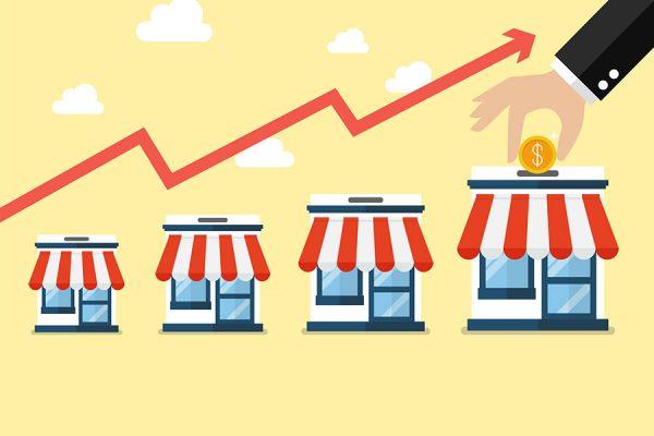 IMagem conceitual sobre franquias mostrando um gráfico feito de loja em crescimento e uma mão de terno colocando uma moeda na última loja como um cofre