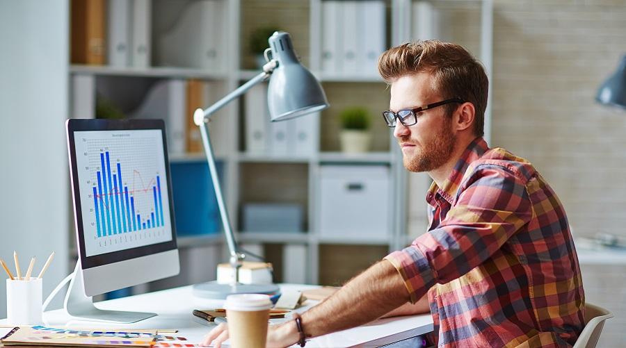 Jovem em home office sentado em frente a um iMac olhando um gráfico. Estudando em uma Pós-graduação a distância