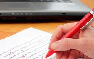 Professor corrigindo prova com caneta vermelha