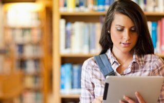 Garota estudante bonita segurando e olhando para um tablet dentro de uma biblioteca
